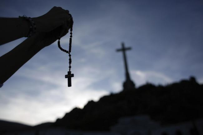 Person holds rosary beads