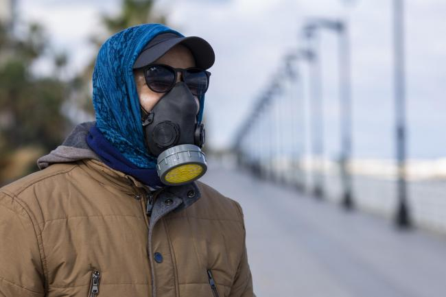 A man wears a tear gas mask to help protect himself from the new coronavirus as he walks at Beirut's seaside corniche, or waterfront promenade, along the Mediterranean Sea, which is almost empty of residents and tourists in Beirut, Lebanon, Saturday,
