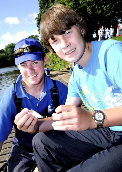 TIPS: Lewis Ryland, aged 13, catches a fish watched by Brad Parkes on a demonstration pitch. 34118302.