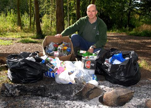 WOODS: Rob Allen of the county's wildlife trust with the rubbish and smouldering ashes party-goers left behind at Tiddesley Wood at the weekend. Picture by Paul Jackson. 38131902