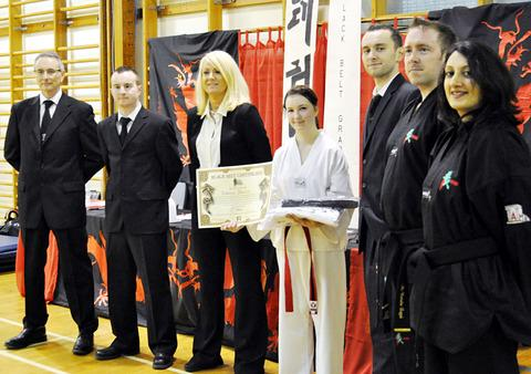 MAKING THE GRADE: London Chinatown Taekwondo's Rebecca Nevin (centre) enjoys her triumph with instructors (left to right) Neil Hall, Gareth Hall, Dee Milbery, Drew Hall, Rich Edkins and Ravindra Luggah. Picture supplied by Neil Hall.