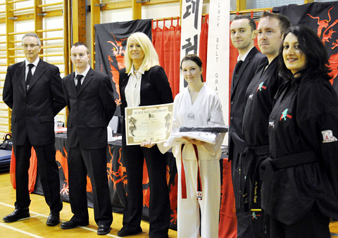 MAKING THE GRADE: London Chinatown Taekwondo's Rebecca Nevin (centre) enjoys her triumph with instructors (left to right) Neil Hall, Gareth Hall, Dee Milbery, Drew Hall, R