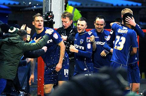 INSTANT ICON: Matt Smith (left) celebrates with his Oldham Athletic team-mates after scoring twice in his side's 3-2 win over Liverpool in the FA Cup fourth round at Boundary Park on Sunday.