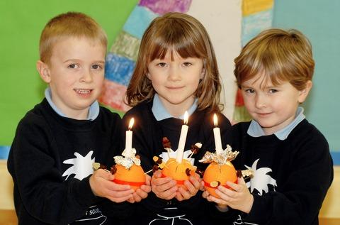 Ben Stanley, Nikki English and Alex Meadows of Fladbury CE Primary School show off the Christingle decorations they made for an annual church service
