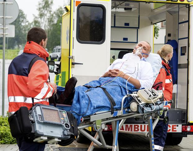 IN THE LINE OF DUTY: An ambulanceman ferries patient in need of oxygen to hospital.