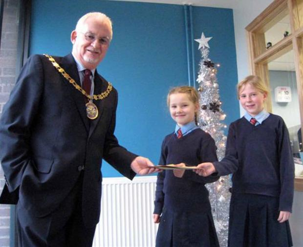 Evesham Journal: WINNERS: Coun Gerry O'Donnell hands gift vouchers to winning card designers Millie Stanley and Grace Plowman.