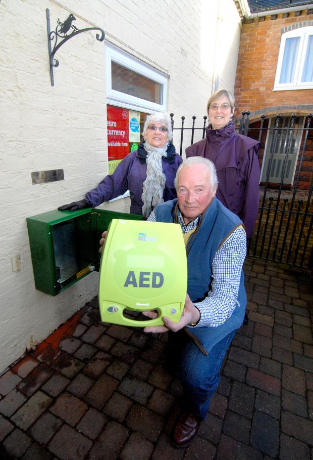 Evesham Journal: 13/01/13. TONY LOCKWOOD (front) from H.F.N. Landscapes with GLORIA RAGBOURNE and EILEEN SYMONDS and the new village defibrillator at The Pantry in Peopleton. Picture by Nick Toogood. (3555554)