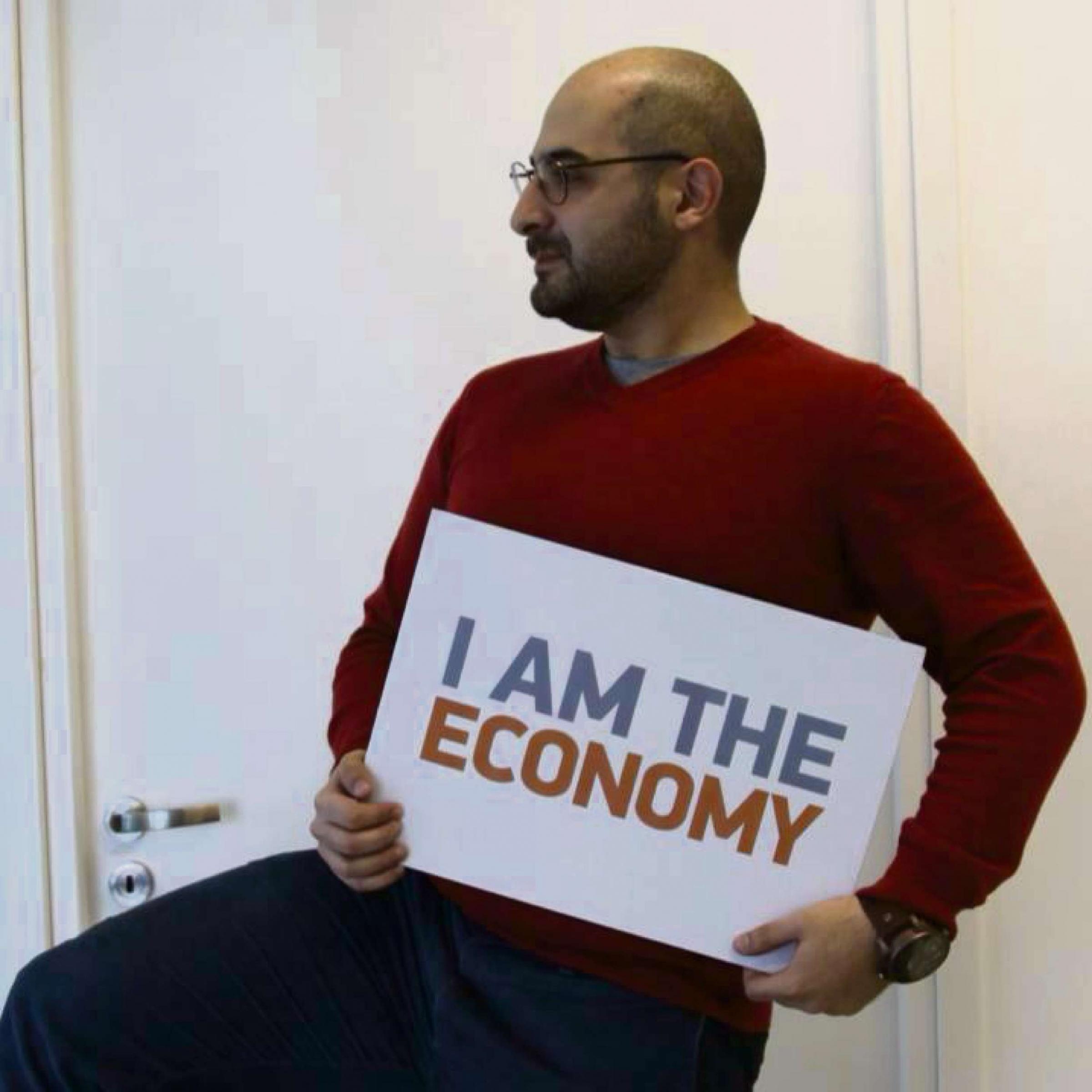 Constantinos Arkadiou holding the I Am The Economy sign he hopes 30,000 other people will take pictures of themselves with