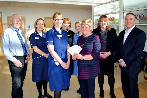 Evesham Journal: Linda Patrick presents her donation to Junior Ward Sister Kerry Burbidge with consultant physician Dr Chris Pycock, specialist nurse Heidi Nunwick, matron Jane Rutter, Matron, staff nurse Rebecca Poile, along with Mr Patrick's daughter Lyn Goodwin a