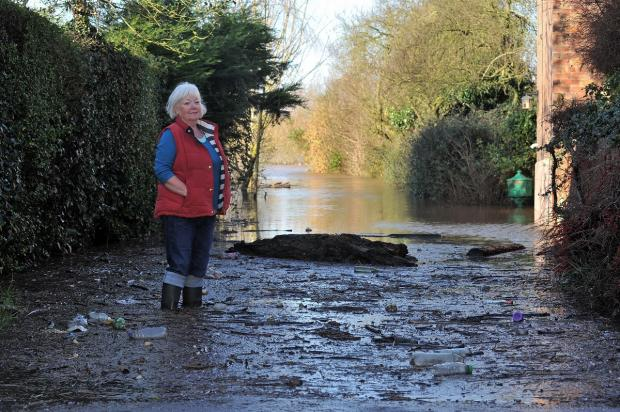 Evesham Journal: Sue Price, resident of Lanes Ends, Kempsey, surveys the flood water at the bottom of the lane. She is also concerned for the welfare of her friend Jacky Smith who is cut off by the flood water.