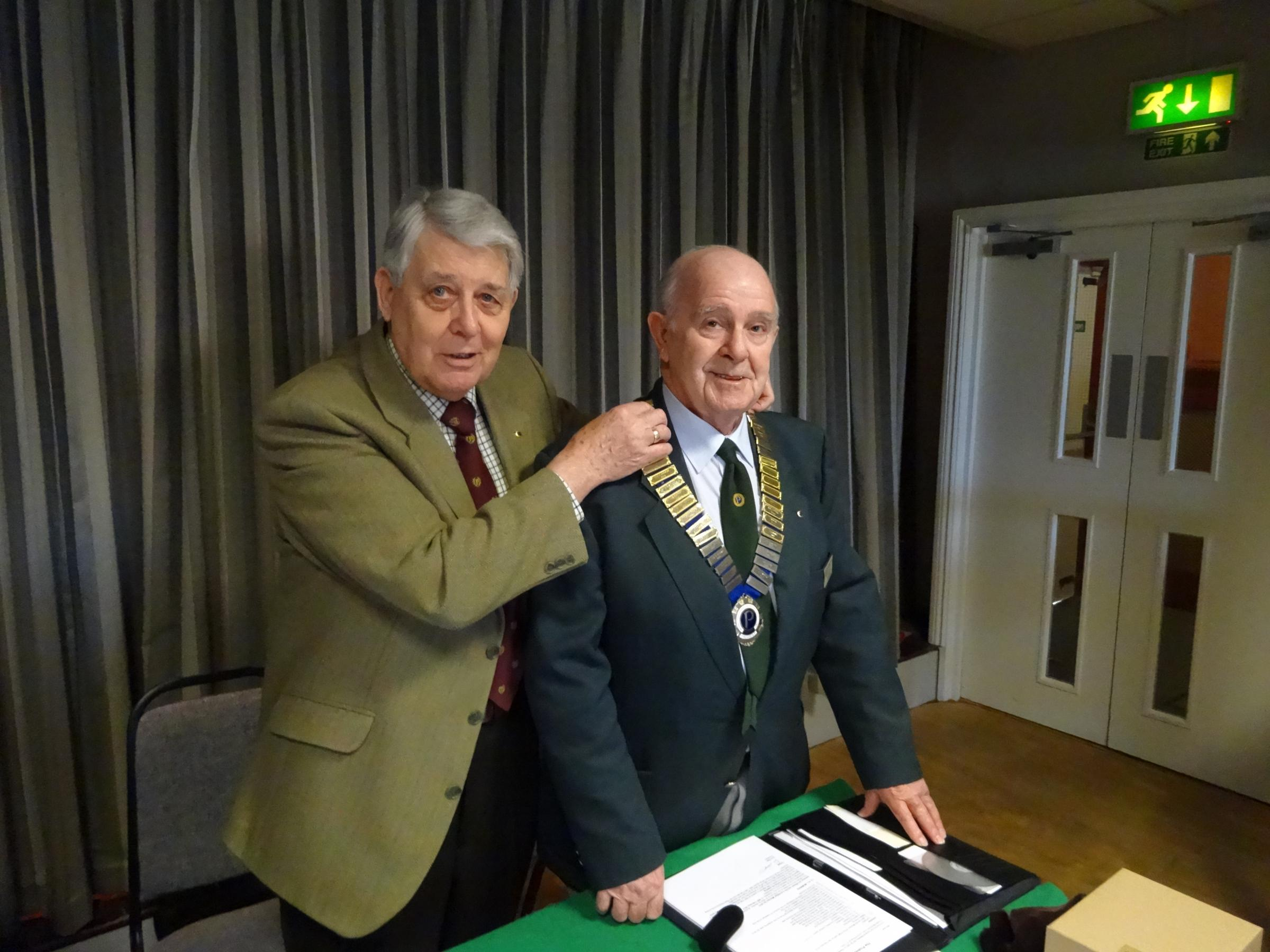 Jim Cox is given the chain by outgoing president Bob Young.