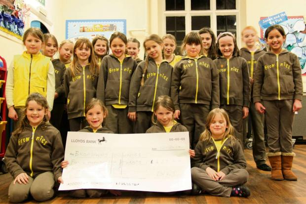 The 1st Broadway Brownies receiving a cheque from the Evesham Round Table