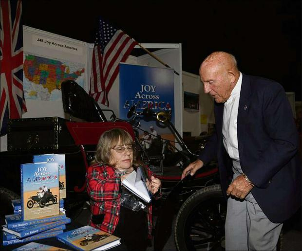 Sir Stirling Moss receiving Joy Rainey's book.
