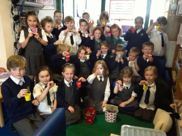 Children filled buckets with notes on how they had helped people during Thinking of Others week at Upton Snodsbury First School.