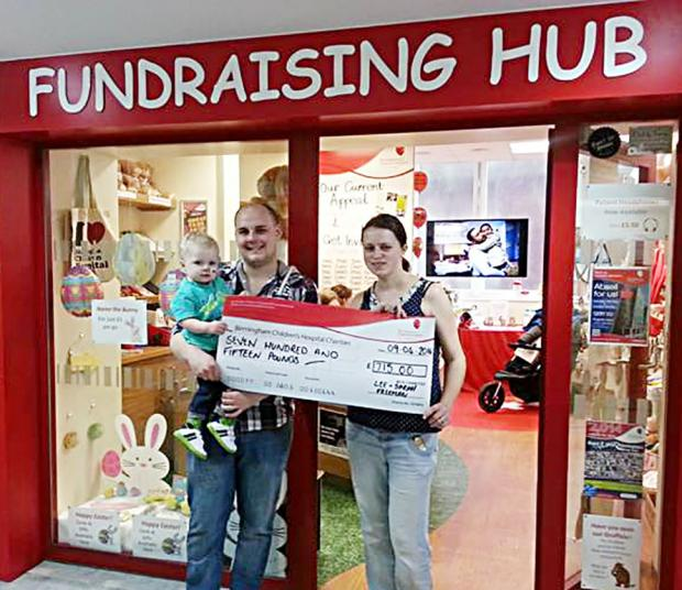 Evesham Journal: Lee and Sarah Freeman with baby Noah as they hand over more than £700 to Birmingham Children's Hospital thanks to generous donations form the good folk of Worcester.