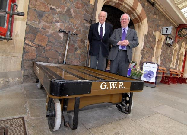Evesham Journal: 1714580301. 22/04/14. Left to right - Rev John Guise and Lord Faulkner of Worcester with one of the three GWR luggage trollies at Great Malvern Railway Station that Rev Guise has restored. Picture by Nick Toogood. (5594289)