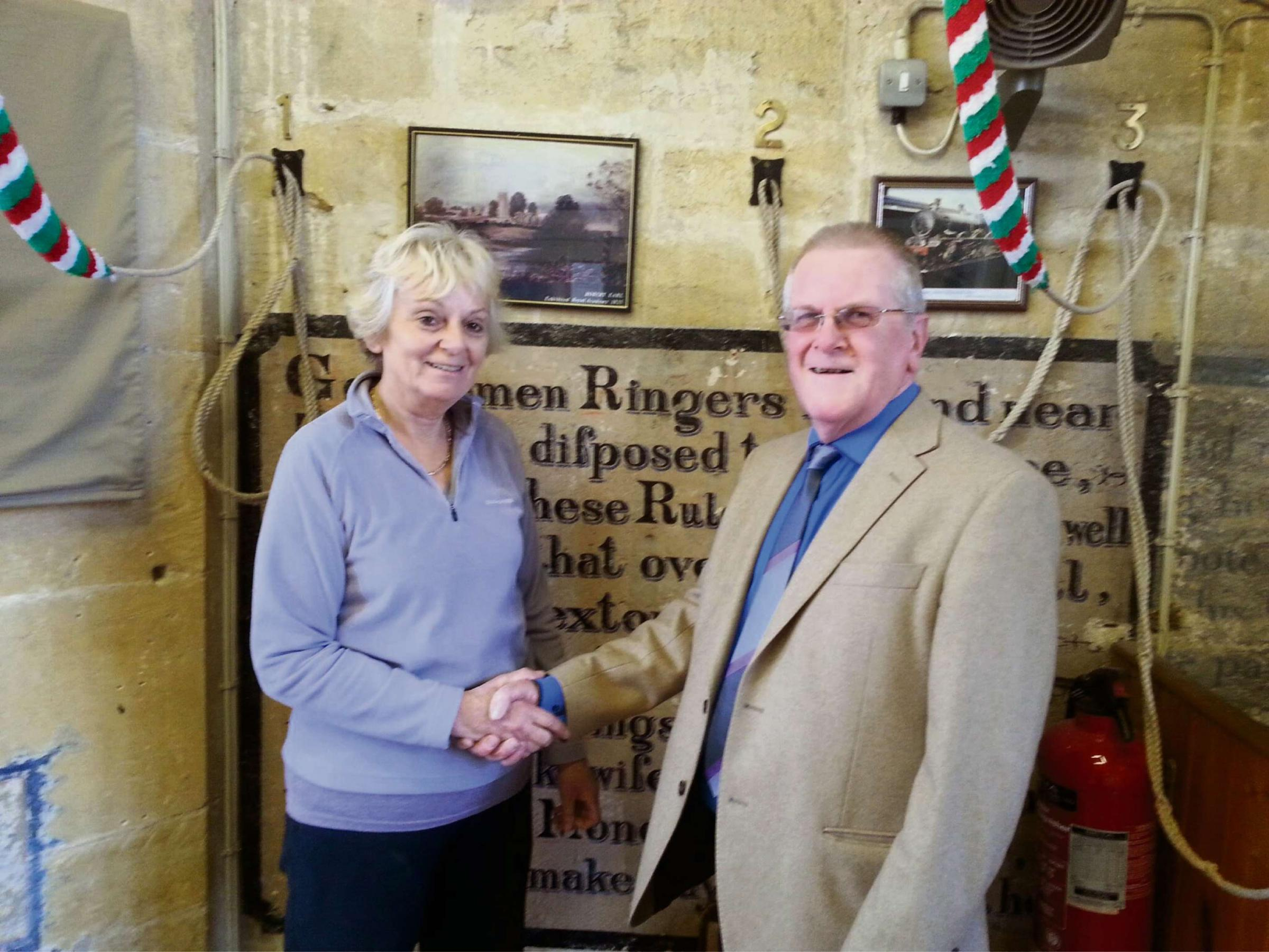 Sue Ablett shaking hands with John Kyte, the chairman of the Vale of Evesham Historical Society.