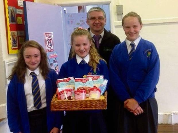 Damien Yates, manager at local, independent Budgens of Broadway recognises students (L-R)Kathryn Albutt, Isla Grelak and Sian as the winners of the store's Bake-enomics competition and presents them with their prize.