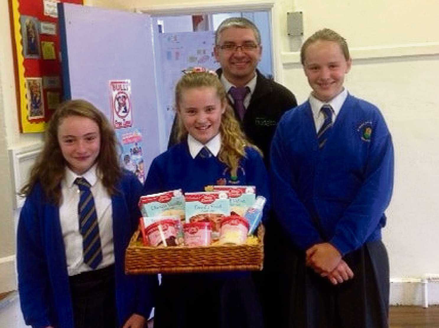 Damien Yates, manager at local, independent Budgens of Broadway recognises students (L-R)Kathryn Albutt, Isla Grelak and Sian as the winners of the store's Bake-enomics