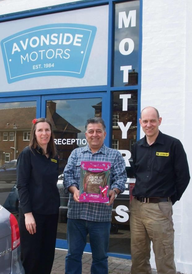 Evesham Journal: Penny Jones (left) and Richard Jones (right), of Cartridge World, present winner Ali Adlkish, of Avonside Motors, with his chocolate prize.