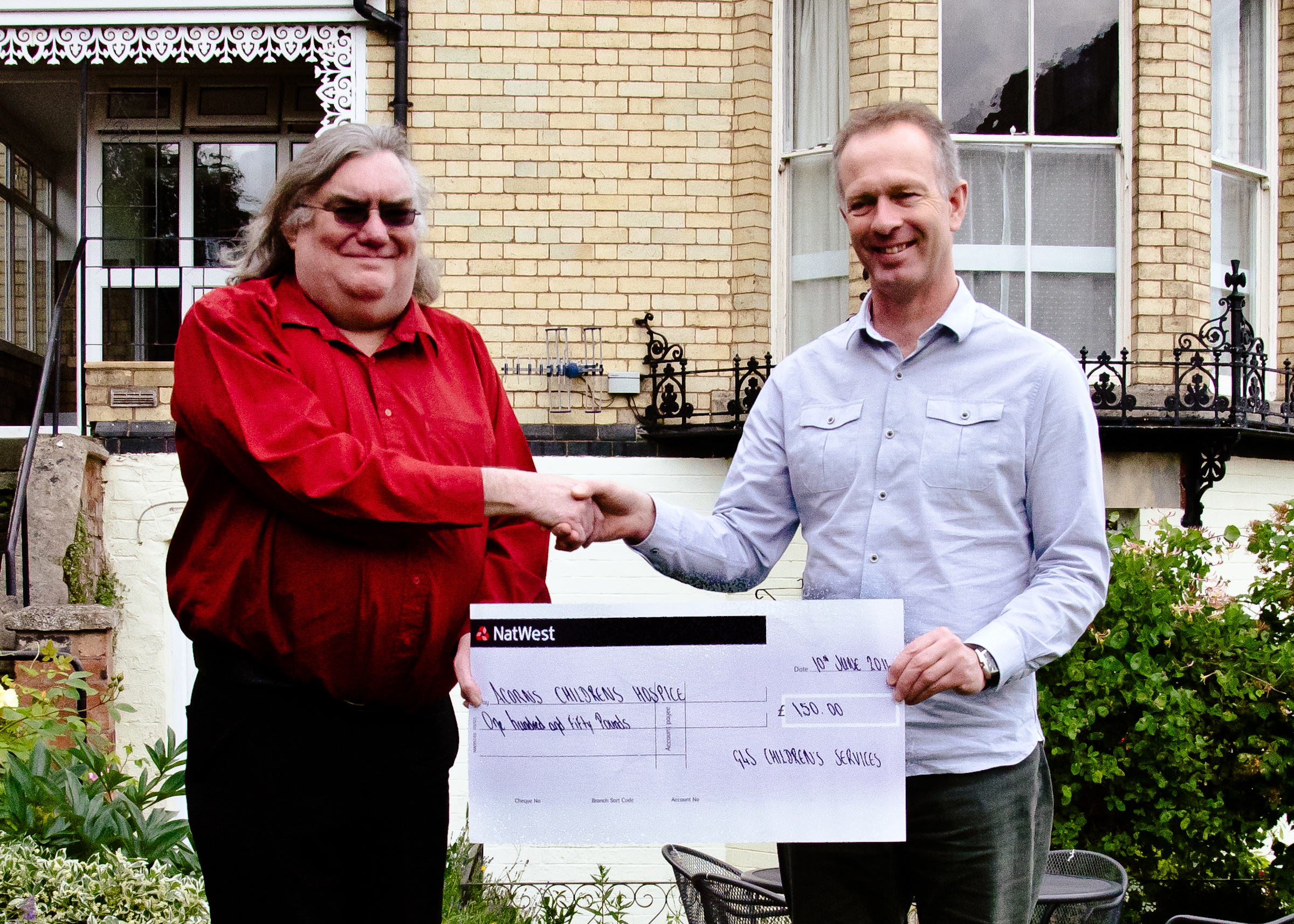 Ian Parker, manager of Malvern's G4S Children's Services in Malvern, presents a cheque for £150 to Andy Mapp, towards the Midsummer Mappfest's support of Acorns Children's Hospice.