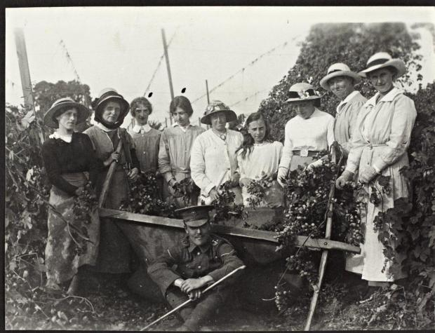 Evesham Journal: LEAVE:  A soldier home on leave during the First World War with pickers in a Worcestershire hop yard