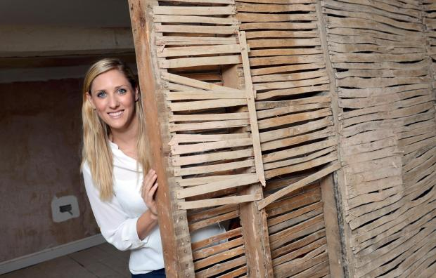 Persora Director Sasha Hyde with the building's original lath which dates back two centuries has now been restored to its former glory.