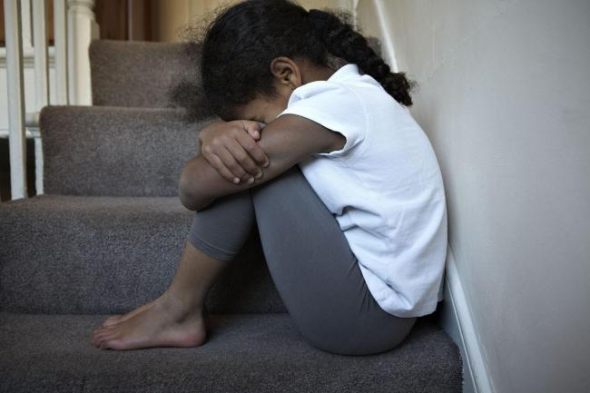 NOTE: PICTURE POSED BY MODEL. Undated handout photo posed by a model issued by the National Society for the Prevention of Cruelty to Children (NSPCC) of a child sitting on some stairs, as the children's charity has launched a campaign to fight childho