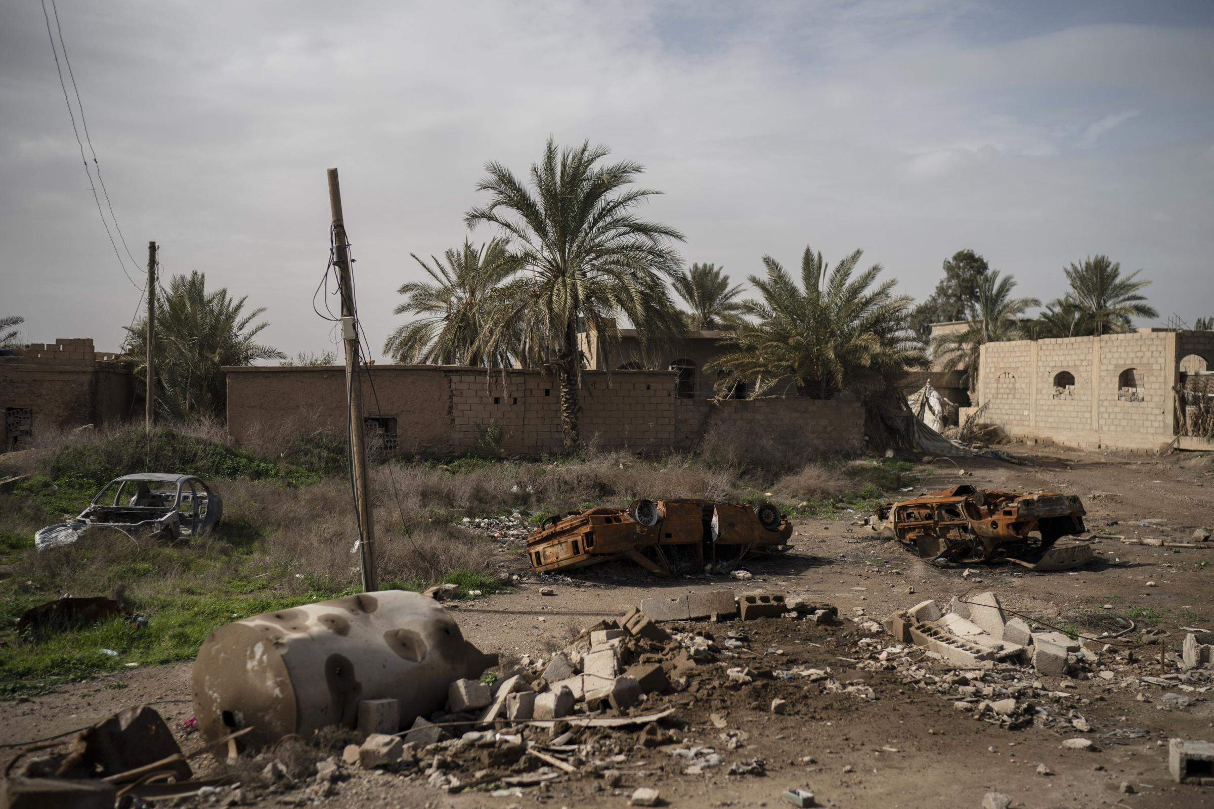 Damaged cars sit in an area recently retaken by US-backed Syrian Democratic Forces from Islamic State militants